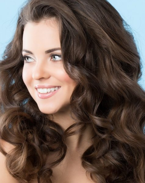Portrait of beautiful girl with long hair waves on a blue background