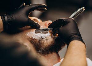 Handsome man cutting beard at a barber shop salon